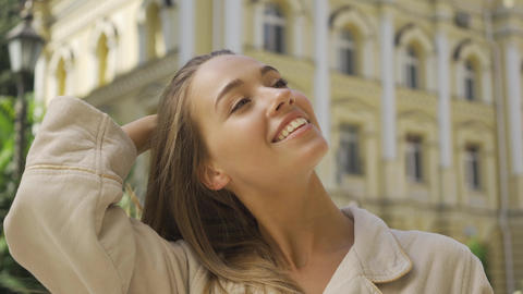 Portrait of smiling young woman sending air kiss looking at camera smiling while Live Action