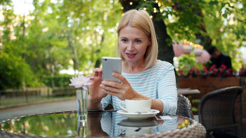 Slow motion of happy woman using smartphone touching screen in outside cafe Footage