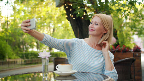 Cheerful lady taking selfie with smartphone camera posing in outdoor cafe alone Footage