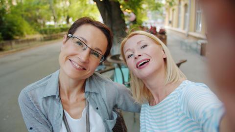 POV of attractive ladies taking selfie outdoors in cafe posing having fun Footage