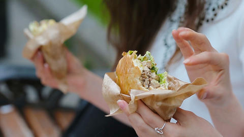 Caucasian women eats hamburger fast food sandwich on the street outdoors. Active Footage