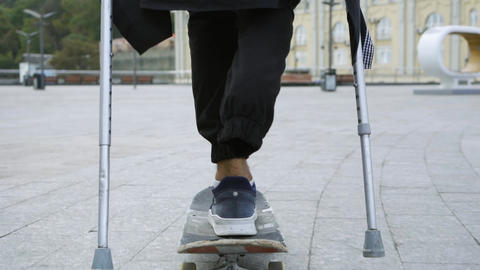 Unrecognized man with one leg on crutches riding on skateboard outdoors. Active Footage