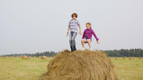 Playful girl and boy jumping on haystack at harvesting field in village. Happy Live Action