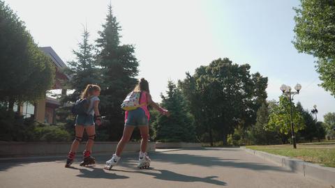 Young active schoolgirls roller skating outdoor Footage