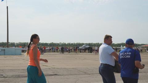People look at the light sports aircraft standing on the airfield Live Action