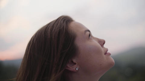Close-up face of young woman with freckles on her face looking up. The girl Live Action