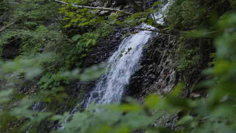 Huge beautiful waterfall in the forest. Beauty of nature, wild nature. Amazing Live Action