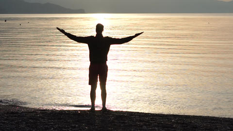 Man raising hands to sunset sky, enjoying life and nature in slow motion Footage