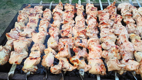 A man's hands rotating the skewers. Shish kebab. Pork or lamb meat pieces being Live Action