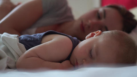 Woman and her small son sleep sweetly together on a large bed in the daytime Live Action