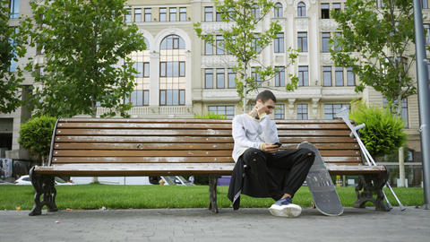 Young man sitting on the bench in the park listening to music on his cellphone Live Action
