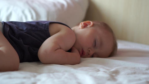 Little sleeping boy is on a large bed with white bedding in slow motion Footage