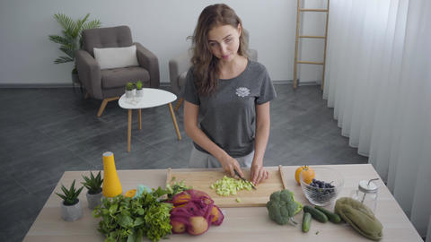 Adorable skill woman cuts a cucumber on a kitchen cutting board with knife while Live Action