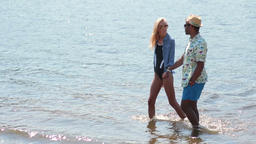 Couple holding hands walking in water on beach Filmmaterial