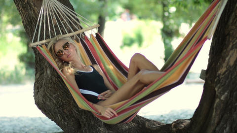 Woman lying in hammock in tree's shadow on beach Filmmaterial
