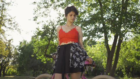Portrait of young woman with short black hair standing in the garden or park Live Action