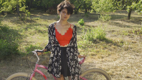 Portrait cute young woman with short black hair standing in the garden or park Live Action