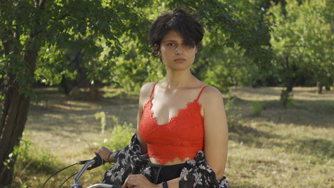 Portrait of pretty young woman with short black hair standing in the garden or Live Action