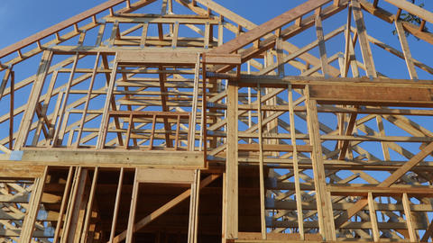 Stick built home under construction under blue sky framing structure wood frame Live Action