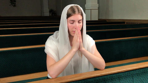 Young religious devoted woman praying in baptist church. Faithful catholic at Live Action
