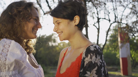 Portrait of two attractive women laughing and rubbing noses close-up. Beautiful Live Action