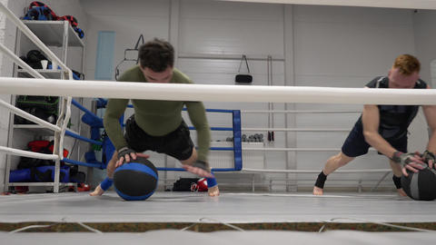 Boxer training push up exercise with medicine ball at boxing ring. Kickboxer man Live Action