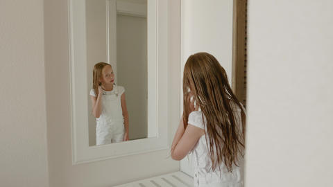 Teenager girl looking wet hair front mirror in bedroom. Young girl with wet hair Footage