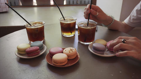 Close up of a girl eats french macaron and drinks espresso tonic beverage Live Action