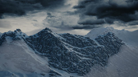 aerial view of snow covered mountains in front of dramatic sky Animation