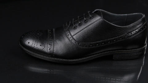 Elegant male shoes with laces stand on a black background with a beautiful Live Action