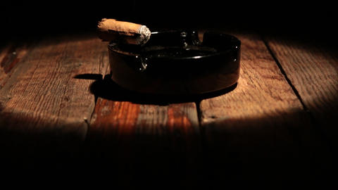 Cigar is lying in an ashtray on a wooden table. Illuminated by the spotlight Live Action