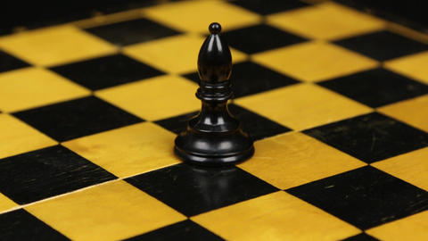 Rotation. Chess figure black bishop on chess board. Close-up Footage