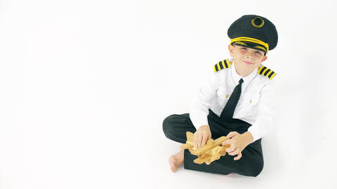 Boy wearing pilot's uniform plays with generic wooden toy plane Live Action