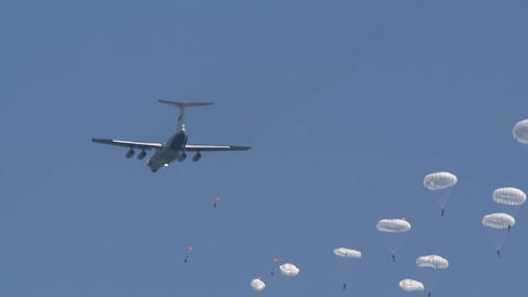 A detachment of military soldiers parachutists descends from the sky to the ground against the blue Live Action