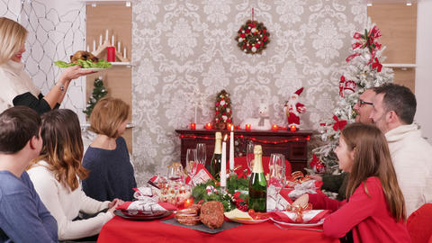Big family gathered around christmas table enjoying traditional food Footage