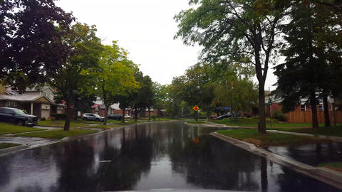 Driving Residential Suburb in the Rain During Day. Driver Point of View POV Suburban Landscape While Footage