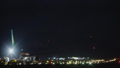 A plane moving on a runway against the pitch black night sky Footage
