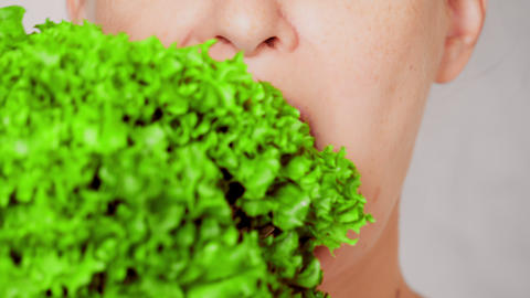 close up face young woman eating leaf vegetable Live Action