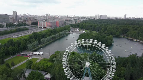An aerial urban view with a green park area with a Ferris wheel in it Footage
