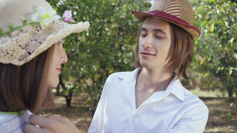 Cute couple in hats standing in the park, the man with long hair touching hair Footage