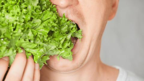 close up face fair man eating leaf vegetable Live Action