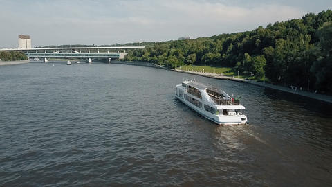 An aerial view of a boat slowly moving on urban river on a sunny day Footage