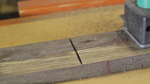 Carpenter renovates a wooden plank with electrical plane close-up Footage