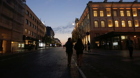 Two young women walking in the night city of Vilnius old town. Walk among the Live Action