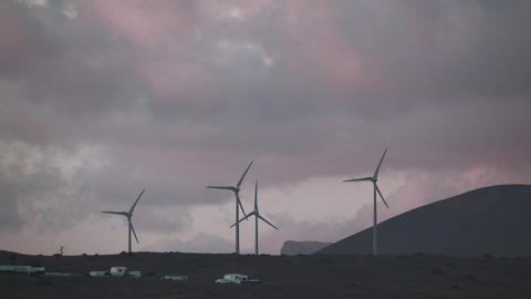 Windmills in the hills, spinning against the colorful evening sky Footage