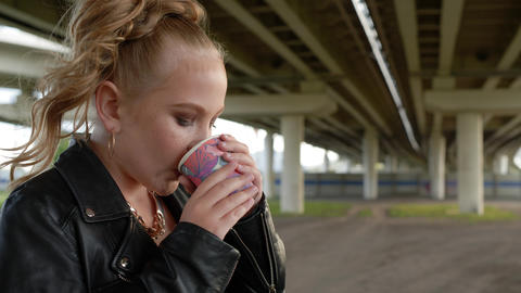 Rock girl drinking hot chocolate at cold day under car bridge. Young beautiful Live Action