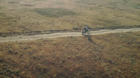 AERIAL: motorcycle rider rides on the sandy ground in the desert. Extreme sports Live Action