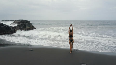 Aerial view of a woman running into water on a black sand beach of Tenerife Live Action