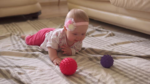 Toddler funny playing with toy ball on floor Live Action