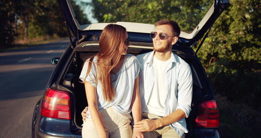 Couple Sitting in Car Trunk and Relaxing Live Action